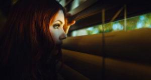 девушка смотрит сквозь жалюзи